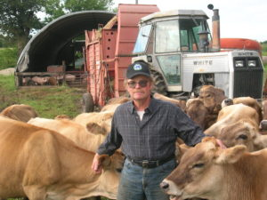 John Gilbert with Gibralter Farms' herd of brown swiss dairy cows.