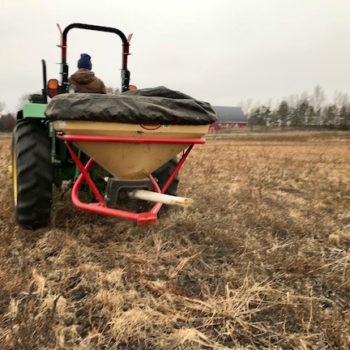 Broadcasting prairie seed with a Vicon® seeder.